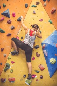 Woman climbing and bouldering indoor in a gym.